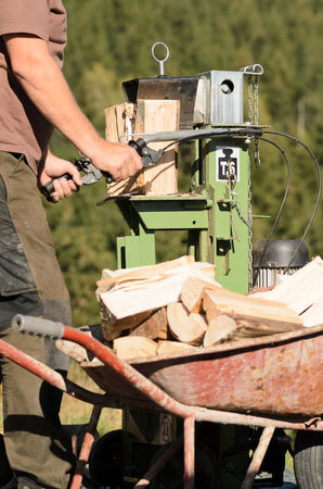 man using electric log splitter
